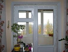 Металлопластиковая балконная штульповая (распашная) дверь. Профиль Rehau (Рехау). Правая створка двери рабочая, левая часть закрыта на шпингалетах, которые легко открываются рычажком на специальном приводе, также в левой створке встроено открываемое окно выполняющее роль форточки. г. Ирпень